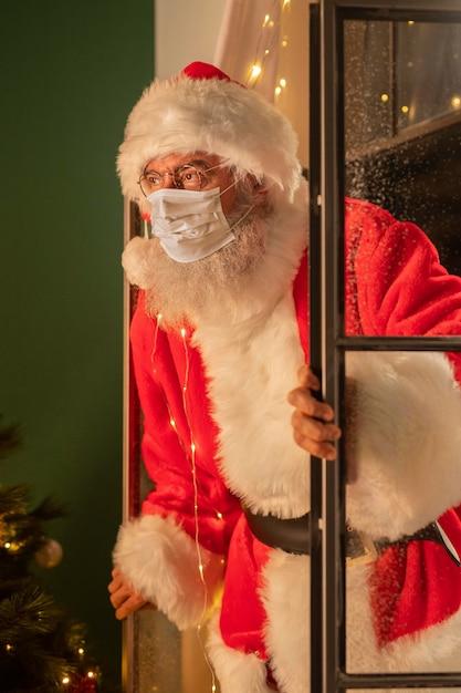 Uomo in costume da babbo natale con mascherina medica che esce dalla finestra Foto Premium