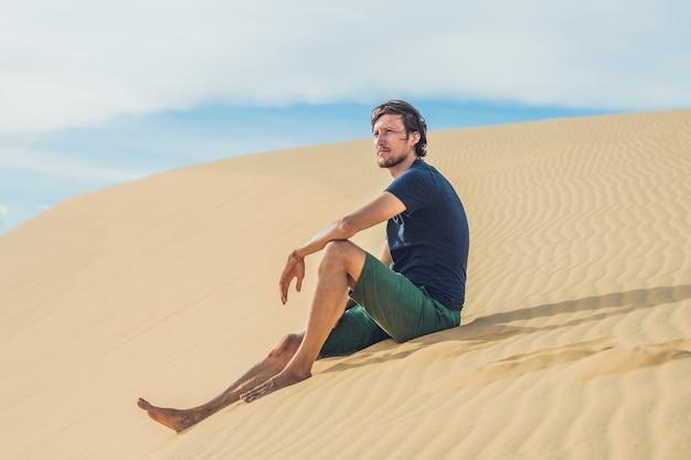Un uomo si siede sulla sabbia nel deserto. Foto Premium