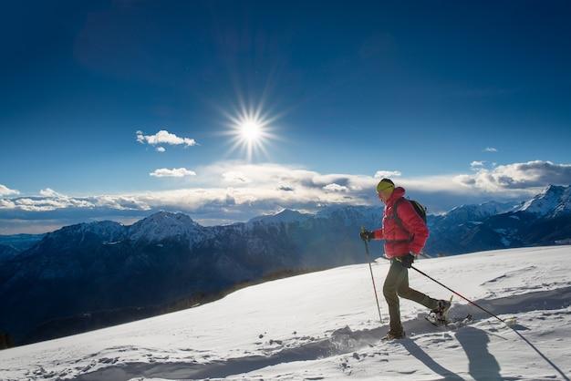 L'uomo con le ciaspole e con i bastoncini da trekking Foto Premium