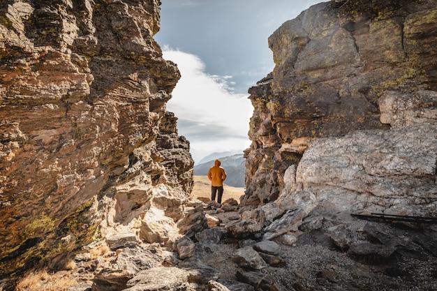 Uomo in piedi su un vertice tra le rocce nel parco nazionale delle montagne rocciose e guardando oltre la catena montuosa in una giornata fredda e ventosa Foto Premium