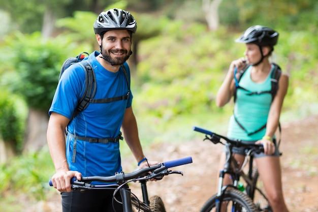 Uomo che sta con il mountain bike in foresta Foto Premium