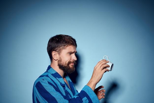 Uomo in abito blu a strisce che tiene in mano la tazza bianca Foto Premium