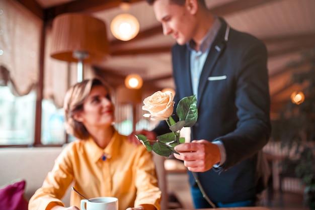 L'uomo in vestito dà fiore di rosa alla giovane donna felice, appuntamento romantico nel ristorante. Foto Premium