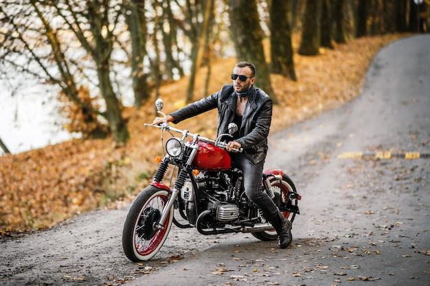 Uomo in occhiali da sole e giacca di pelle che si siede su una moto sulla strada Foto Premium