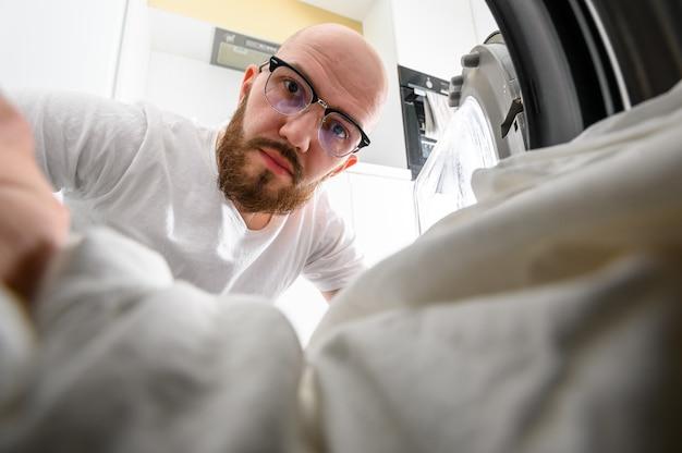 L'uomo tira fuori l'interno di una lavatrice Foto Premium