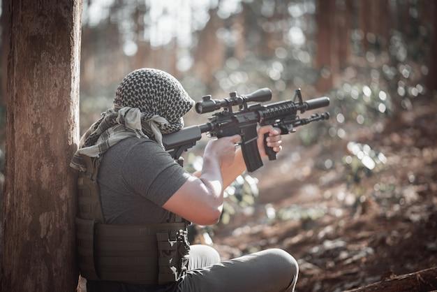 Equipaggi il terrorista che indossa una maschera e che tiene una pistola, concetto del terrorista Foto Premium