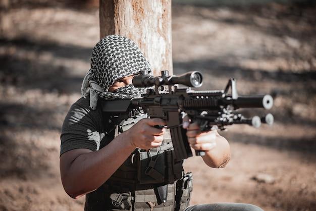 Uomo terrorista che indossa una maschera e in possesso di una pistola, terrorista concpet Foto Premium
