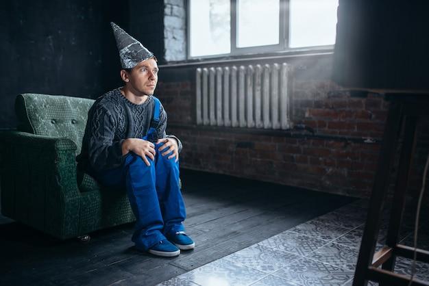 Uomo con cappuccio di carta stagnola guarda la tv, fobia della telepatia Foto Premium