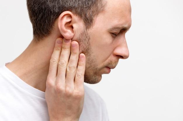 L'uomo tocca le ghiandole linfatiche con le dita vicino all'orecchio Foto Premium
