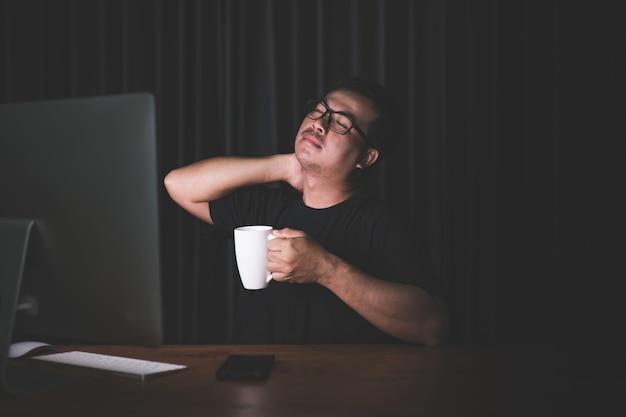 Uomo che si tocca il collo a causa del dolore dovuto al lavoro sul computer Foto Premium