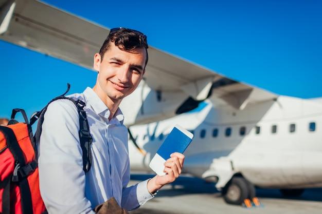 Imbarco del viaggiatore dell'uomo sul passaporto della tenuta dell'aereo. passeggero felice con zaino andando in vacanza Foto Premium