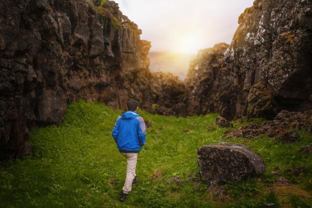 Viaggiatore dell'uomo che fa un'escursione attraverso il paesaggio dell'islanda. Foto Premium
