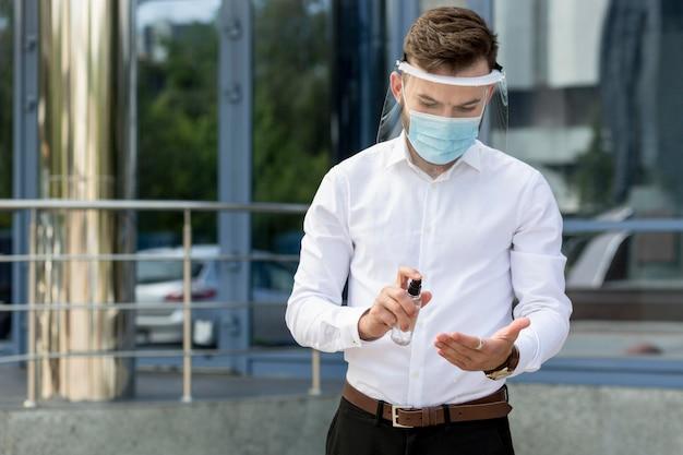 Uomo che utilizza disinfettante per le mani Foto Premium