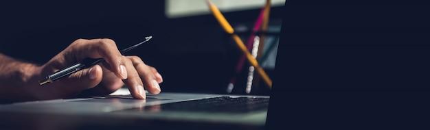 Un uomo che per mezzo del computer portatile che lavora alla nuova idea di progetto nell'ufficio a tarda notte Foto Premium