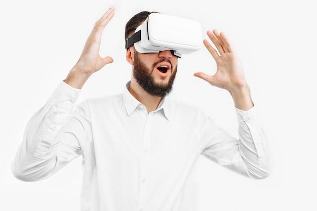 Un uomo con gli occhiali virtuali, primo piano, su un muro bianco Foto Premium