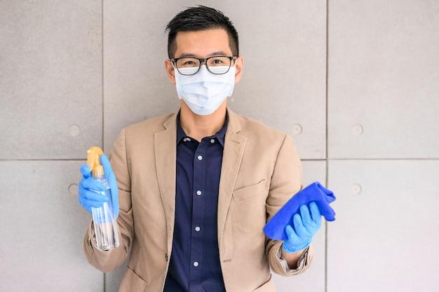 Equipaggi la maschera e i guanti d'uso della tenuta che tengono lo spruzzo dell'alcool e il panno della microfibra Foto Premium