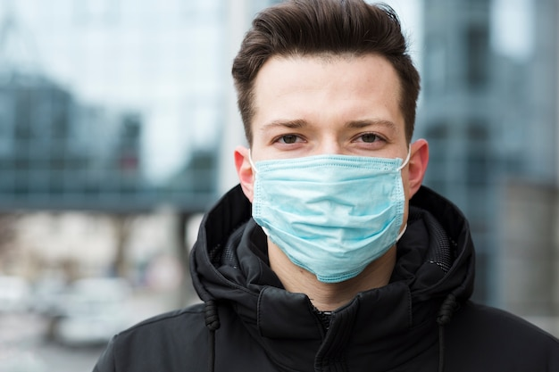 Uomo che indossa una maschera medica in città Foto Premium