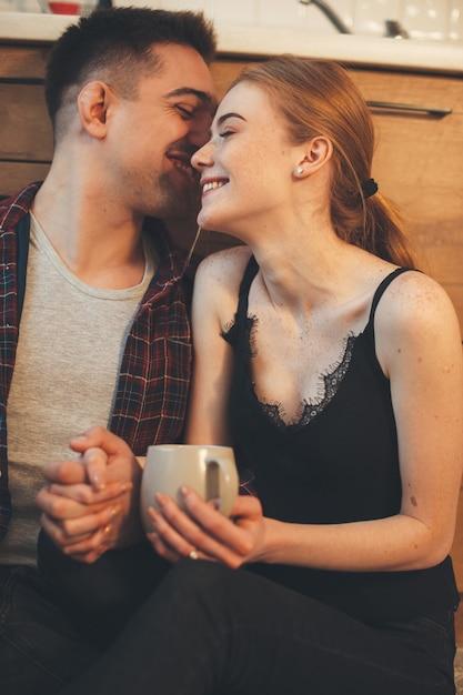 Uomo che bisbiglia qualcosa a sua moglie mentre si prende una pausa caffè in cucina sul pavimento Foto Premium