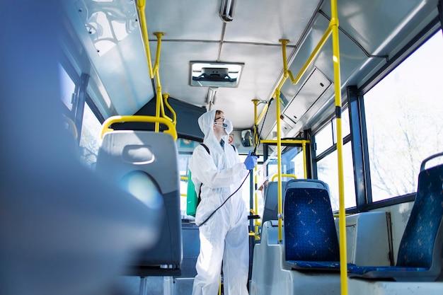 Uomo in tuta di protezione bianca che disinfetta il manubrio dell'interno dell'autobus per fermare la diffusione del virus corona altamente contagioso Foto Premium