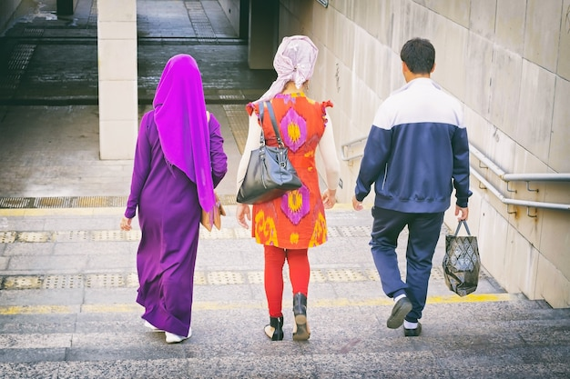 Un uomo con una borsa e due amiche in hijab e abiti nazionali giù per le scale fino al sottopasso Foto Premium