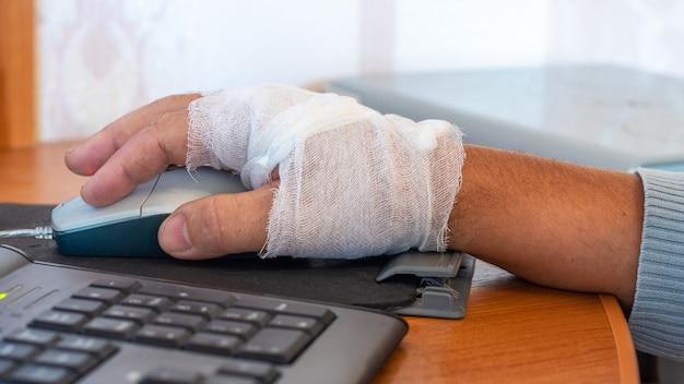 L'uomo con una mano fasciata lavora al computer Foto Premium