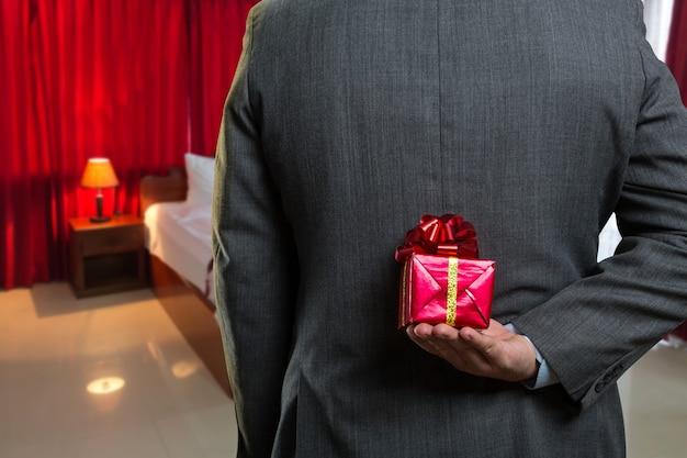 Uomo con un regalo dietro la schiena Foto Premium