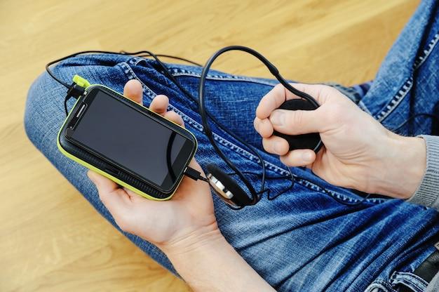 Uomo con una cuffia, uno smartphone e un power bank Foto Premium