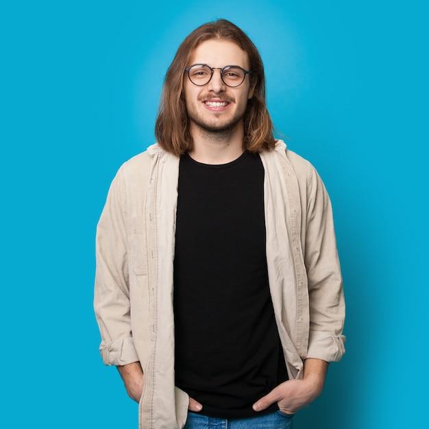 Uomo con i capelli lunghi e la barba che indossa occhiali da vista sorride alla telecamera su una parete blu dello studio Foto Premium