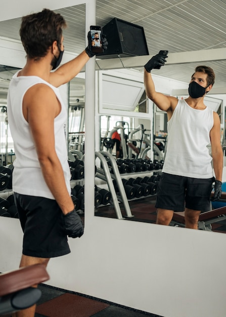 Uomo con mascherina medica prendendo un selfie in palestra Foto Premium