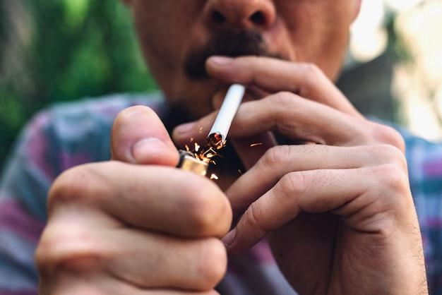 Uomo con baffi e barba accendere una sigaretta Foto Premium
