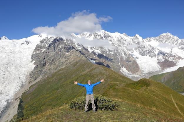 Uomo con le mani alzate in piedi sulle montagne innevate Foto Premium