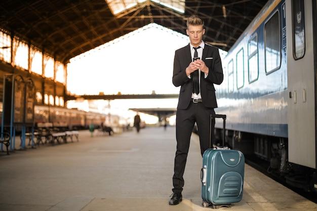 Uomo con carrello nella stazione ferroviaria Foto Premium