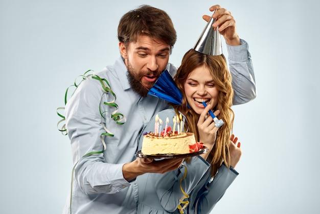 Un uomo e una donna per un compleanno con un cupcake e una candela in un berretto festivo si divertono e celebrano la vacanza insieme Foto Premium