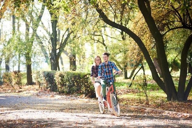 Uomo e donna in bicicletta insieme sulla doppia bici in tandem Foto Premium