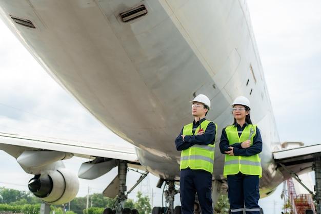 Uomo e donna ingegnere manutenzione aereo braccio incrociato Foto Premium