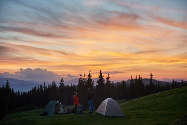 Uomo e donna che hanno un periodo di riposo nel campeggio vicino a due tende in montagna durante un'escursione insieme ai loro zaini godendo bel tramonto Foto Premium