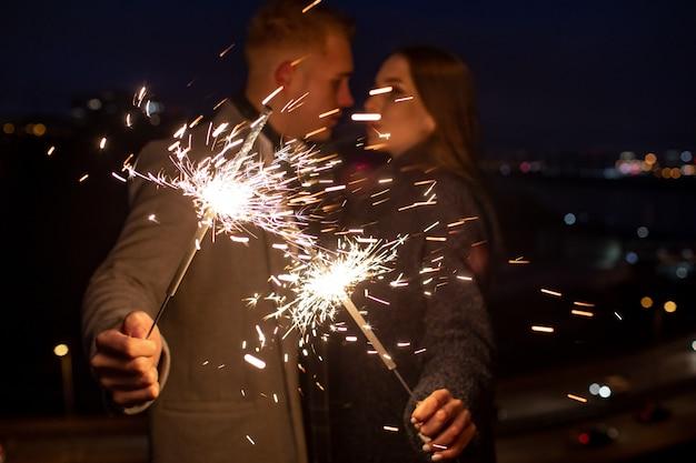 Uomo e donna che tengono una stella filante bruciante. fuoco del bengala Foto Premium