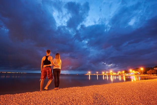 Uomo e donna che riposano su pebble beach al crepuscolo sul fondo blu drammatico del cielo nuvoloso dell'acqua calma Foto Premium