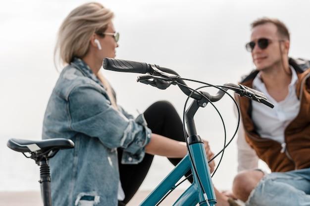 Uomo e donna che parlano accanto a una bici fuori Foto Premium