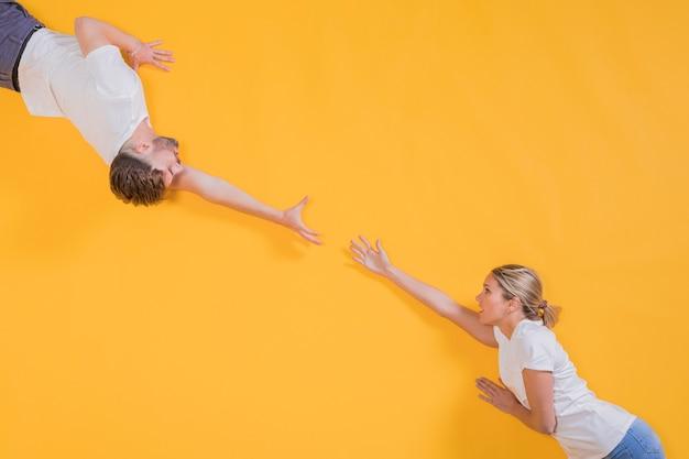 Uomo e donna che cercano di raggiungere l'altro Foto Premium