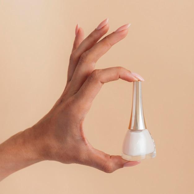 Cura sana del manicure che tiene uno smalto per unghie Foto Premium