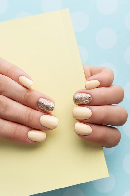 Mani della donna curate con manicure gialla alla moda in stile minimal. Foto Premium