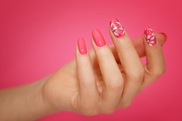 Unghie della donna curate con nailart rosa con fiori. manicure per unghie. Foto Premium