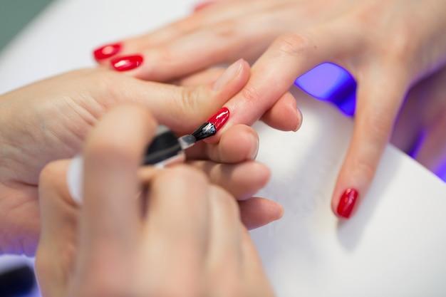 Il maestro del manicure fa il manicure rosso sulla mano della giovane donna. maestro del chiodo della donna che fa le unghie a un cliente della ragazza in un salone di bellezza. prenditi cura delle mani Foto Premium