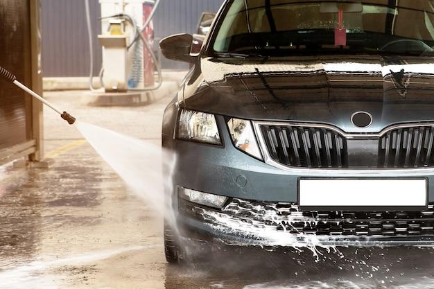 Autolavaggio manuale con acqua pressurizzata in autolavaggio esterno.pulizia auto con acqua ad alta pressione. autolavaggio - con getto d'acqua al servizio di autolavaggio Foto Premium