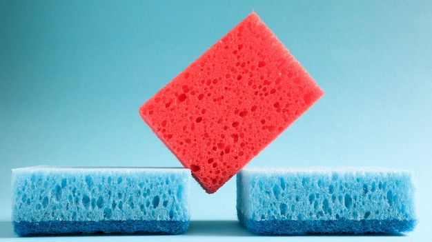 Molte spugne blu, rosse, gialle, verdi vengono utilizzate per lavare e pulire lo sporco usato dalle casalinghe nella vita di tutti i giorni Foto Premium