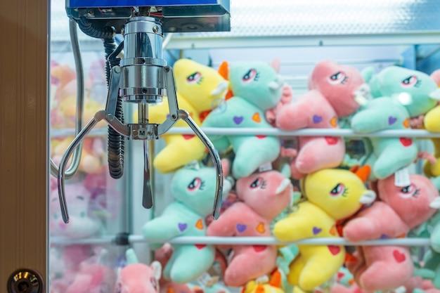 Molte bambole colorate metti nel cabinet claw game aspetta che le persone giochino. Foto Premium