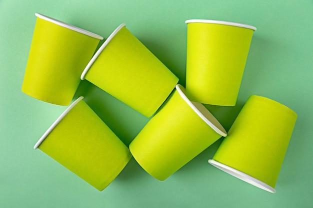 Molte tazze di carta verde usa e getta vuote per caffè o tè da asporto senza coperchi si trovano sullo sfondo Foto Premium