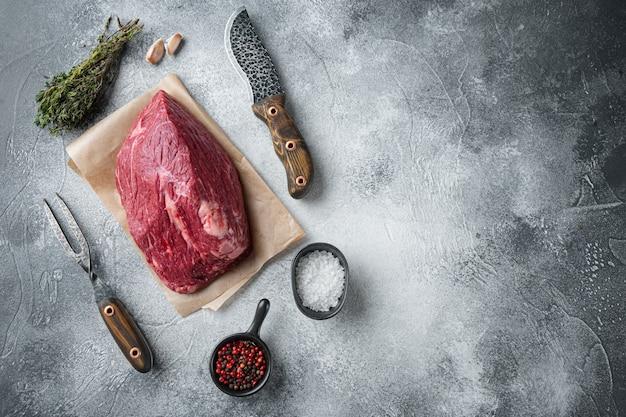 Manzo in marmo crudo impostato con il vecchio coltello da macellaio mannaia, sul tavolo grigio, vista dall'alto laici piatta Foto Premium
