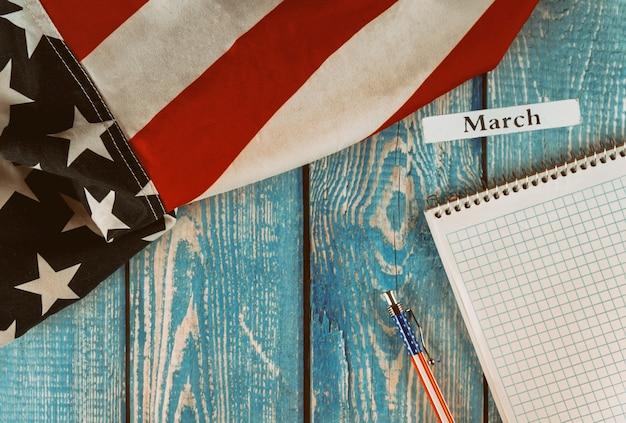 Mese di marzo dell'anno civile bandiera degli stati uniti d'america del simbolo di libertà e democrazia con il blocco note e la penna in bianco sulla tavola di legno dell'ufficio Foto Premium